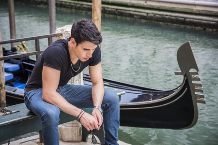 dark haired: Portrait of Attractive Dark Haired Young Man Sitting on Bench Next to Narrow Canal in Venice, Italy, with Traditional Gondola