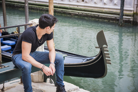 Portrait of Attractive Dark Haired Young Man Sitting on Bench Next to Narrow Canal in Venice, Italy, with Traditional Gondola