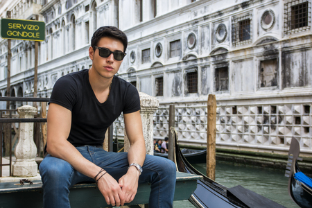 dark haired: Portrait of Attractive Dark Haired Young Man Leaning Against Railing on Foot Bridge Over Narrow Canal in Venice, Italy Stock Photo