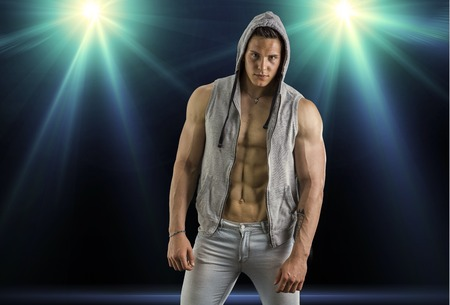 hooded vest: Confident, attractive young man with open vest on muscular torso, ripped abs and pecs. On dark background with spotlights above