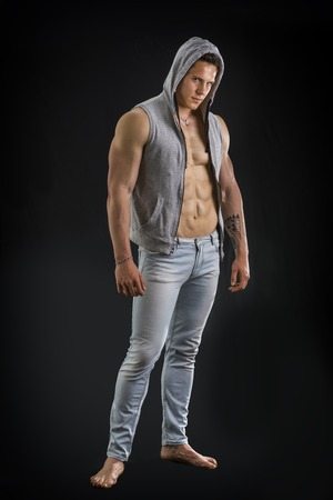 hooded vest: Confident, attractive young man with open vest on muscular torso, ripped abs and pecs. Isolated on black Stock Photo
