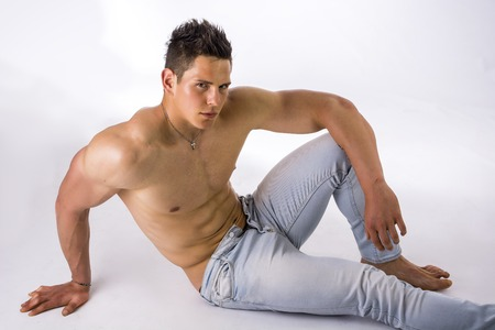 laying abs exercise: Handsome young bodybuilder laying down on the floor, showing ripped abs, muscular pecs, arms, shot from above