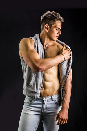 Confident, attractive young man with open vest on muscular torso, ripped abs and pecs. Isolated on black Stock Photo