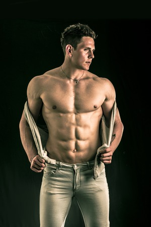 pecs: Confident, attractive young man with open vest on muscular torso, ripped abs and pecs. Isolated on black Stock Photo