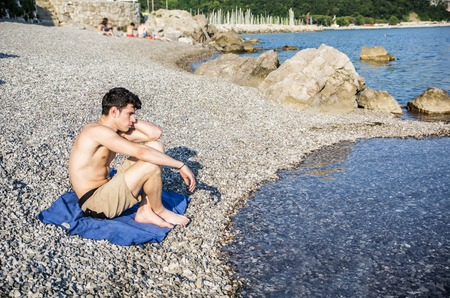 Handsome young man on beach in a sunny day, sitting on a gravel, thinking or meditating Stok Fotoğraf