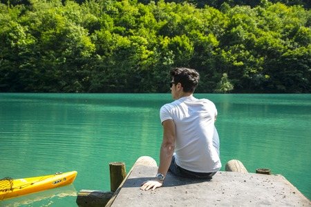 Handsome young man on a lake in a sunny, peaceful day, sitting on a pier, thinking or relaxing and enjoying the landscape Foto de archivo