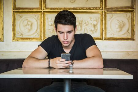 typing man: Young handsome man sitting in elegant cafeteria or restaurant using cell phone to send text message Stock Photo