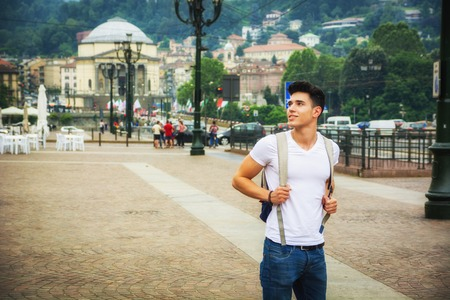 ruck sack: Handsome young man walking in European city square, Piazza Vittorio Veneto in Turin, Italy