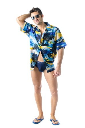full figure: Attractive, muscular young man smiling, wearing open hawaian style shirt, swimming suit and sunglasses. Full figure shot