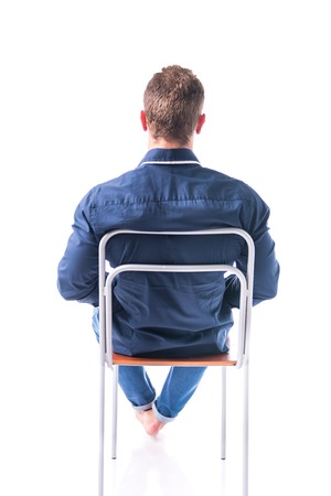 Back of barefoot young man sitting on chair, isolated on white background
