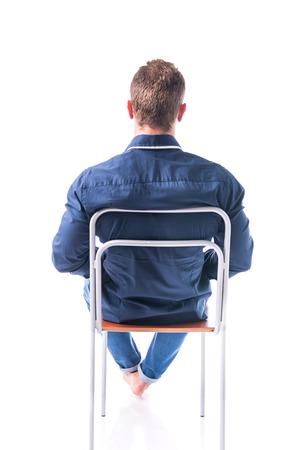 Terug van blote voeten jonge man zittend op een stoel, geïsoleerd op een witte achtergrond