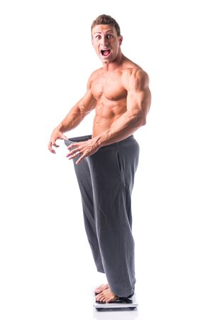 muscle guy: Shirtless young male bodybuilder has lost weight, wearing large pants. Smiling, isolated on white Stock Photo