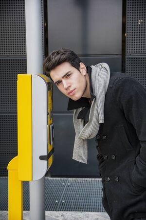 bending down: Apuesto joven elegante agacharse mirando dentro de una puerta de entrada de cristal en un edificio con altavoz del tel�fono al lado, la vista lateral