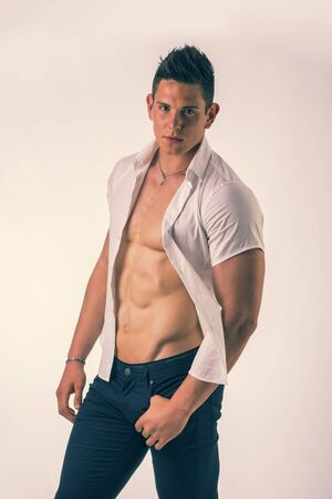 open shirt: Young man displaying his muscular torso holding open his stylish shirt with his hands while looking at camera, smiling, on light background Stock Photo