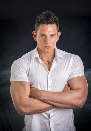 severe: Handsome young man with elegant shirt, looking at camera, isolated on black, with severe expression and arms crossed on chest Stock Photo