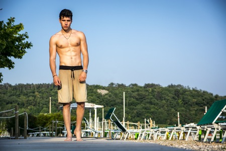 Attractive young shirtless athletic man standing at the beach, wearing shorts