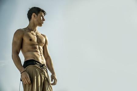 shirtless: Muscular hombre joven de pie sin camisa contra el cielo azul, visto desde abajo en perspectiva