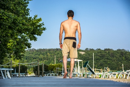 nue plage: Retour d'un jeune homme athlétique torse nu marchant sur la plage, en short, en aller Banque d'images