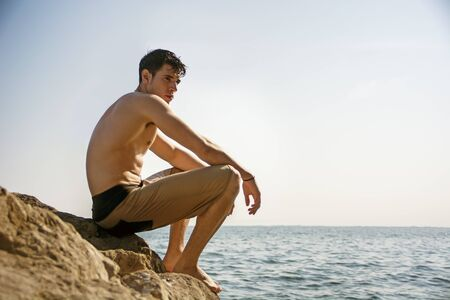 Attractive handsome young man sitting on rock by sea or ocean shore with wet hair, looking in the distance, profile view Stock Photo