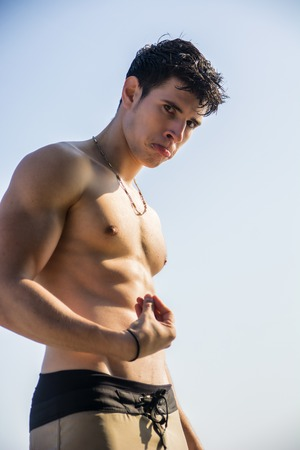 Muscular young man shirtless standing against blue sky, seen from below perspective, doing Italian gesture for What Is It Stock Photo