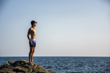 beach hunk: Muscular young man shirtless standing on rock with sky and sea or ocean behind. Large copyspace Stock Photo