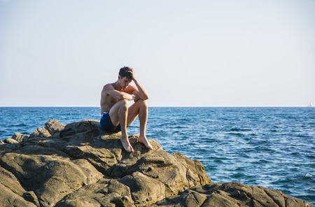 beach hunk: Muscular young man shirtless sitting on rock with sky and sea or ocean behind. Large copyspace Stock Photo
