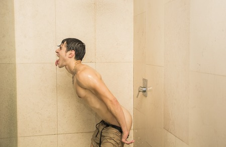 nude ass: Close up Attractive Young Bare Muscular Young Man Taking Shower Sticking Out Tongue and Uncovering Bottocks