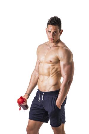 männer nackt: Athletischen muskulösen mit nacktem Oberkörper junger Mann mit Protein-Shake-Flasche, bereit zum Trinken. Isoliert auf weiß, Blick in die Kamera Lizenzfreie Bilder