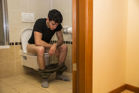 defecating: Young Dark Haired Man Sitting on Toilet with Pants Around Ankles