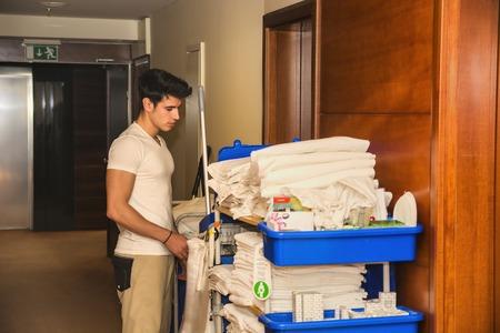 orden y limpieza: Hombre joven empujando un carrito de la limpieza cargados de toallas limpias, ropa y equipo de limpieza en un hotel, ya que los servicios de las habitaciones