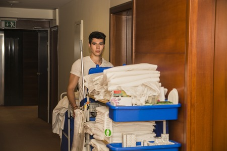 hotel hall: Young man pushing a housekeeping cart laden with clean towels, laundry and cleaning equipment in a hotel as he services the rooms