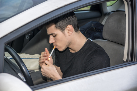 injurious: Handsome Young Man smoking cigarette while Driving a Car Stock Photo