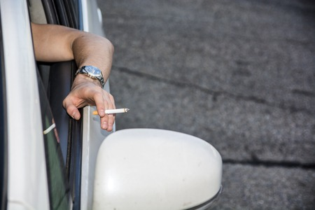 Handsome Young Man smoking cigarette while Driving a Car Stock Photo