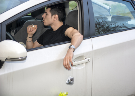 Detail of Man Wearing Wrist Watch Tossing Crumpled Ball of Refuse Out of Car Window onto Ground, Close Up of Irresponsible Man Littering Garbage from Car