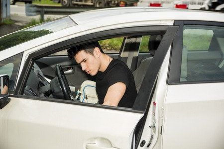 getting out: Young attractive man getting out of white car, opening the door Stock Photo