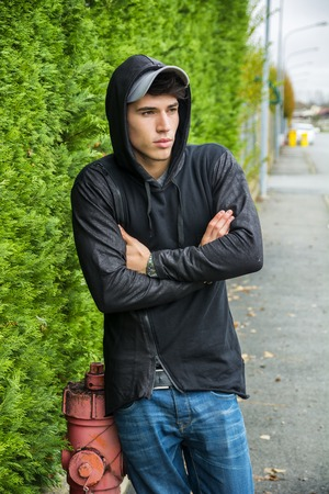 beau mec: Handsome young man in black hoodie sweater standing outdoor in street looking away to a side, arms crossed on chest
