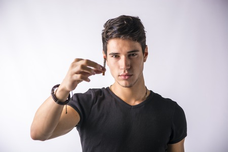 looking at viewer: Handsome young man looking at his cigarette, presenting it to the camera and offering to the viewer, on light background