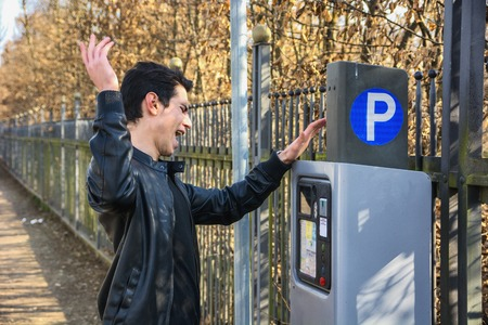 Young man angry at parking ticket to be dispensed from the ticket booth at the side of a street after making his payment Standard-Bild