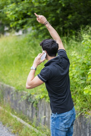 hailing: Young handsome man on side of a road, calling on cell phone and waiting for taxi cab