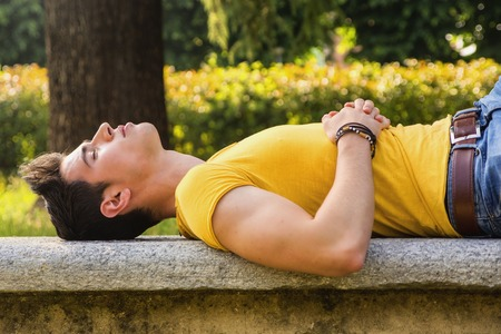 during the day: Attractive young man sleeping on stone bench outdoor in city park during day Stock Photo