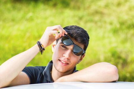 young male model: Head and arms shot of handsome attractive young man looking at camera outdoor, leaning on flat surface with head resting on hands Stock Photo