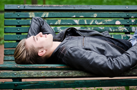 man lying down: Handsome blond young man lying down on green, wooden park bench, looking up