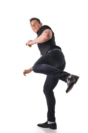 looking towards camera: Full length shot of young muscular big man kicking towards camera, wearing stylish black shirt and black jeans looking at camera, isolated on white
