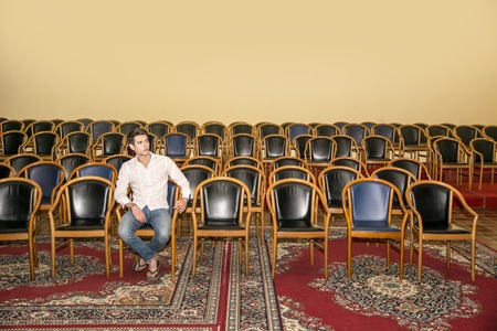 Handsome Young Man in Casual Wear, Sitting at the Audience Chair In Front of a Podium Alone and Looking at the Camera. Stock Photo