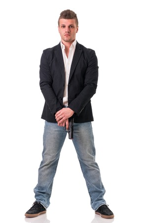 agent de sécurité: Homme élégant avec un pistolet, vêtu comme un espion ou un agent secret, avec des écouteurs, isolé sur blanc. Figure de plein fouet Banque d'images