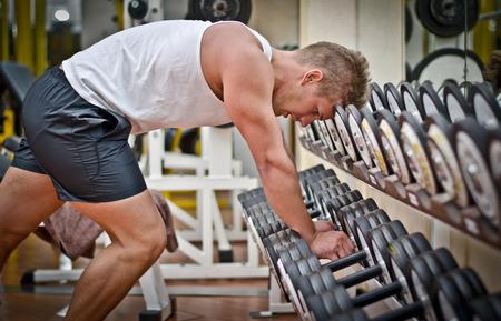 deportista: Hombre atl�tico joven hermoso que descansa sobre dumbells estante despu�s de entrenamiento en el gimnasio Foto de archivo