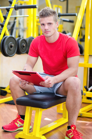 adult  body writing: Young male personal trainer holding clipboard, sitting on training equipment in gym