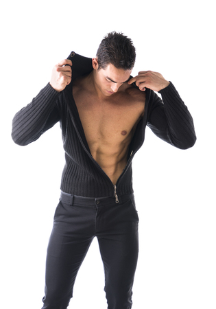pecs: Confident, attractive young man with open sweater on muscular torso, ripped abs and pecs