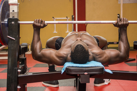 naked male body: Hunky muscular black bodybuilder working out in gym, exercising pecs on bench with barbell
