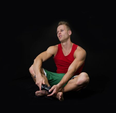 liesure: Young Muscled Man Sitting on Floor Holding Joystick with Disappointed Expression on Face. Isolated on Black.